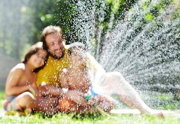 Father having fun with his little sons holding water sprinkler-1